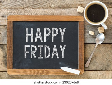 Happy Friday sign on Blackboard. Blackboard with Happy Friday sign and cup of coffee on wooden background