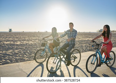 happy friend bicycling together on sunny summer beach in california usa