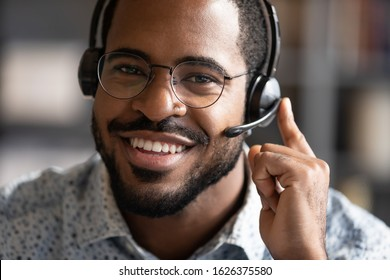 Happy friendly african ethnic business man telemarketing operator wear wireless headset microphone looking at camera, customer support service assistant on call center phone closeup headshot portrait