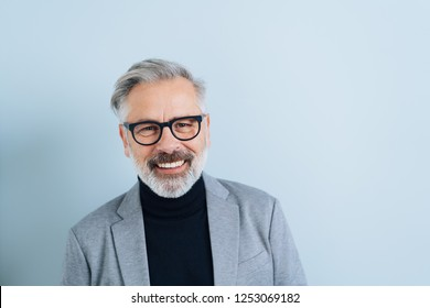 Happy friendly bearded man wearing glasses grinning at the camera in a head and shoulders portrait on white