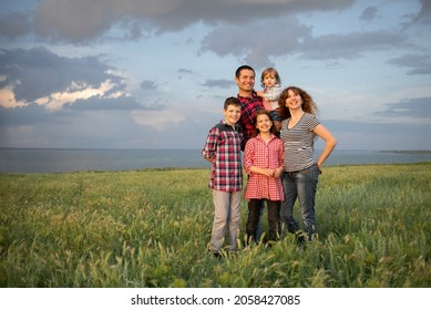 Happy friendly big family with three children two sons and a daughter stand in the summer at sunset background of the cloudy blue sky in the evening.