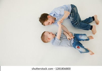Happy and friendly brothers during the game. Two Emotional and Positive Little Boys Frolic and Tickle Each Other Laughing While Lying on the White Floor. Happy childhood. Positive emotions and energy