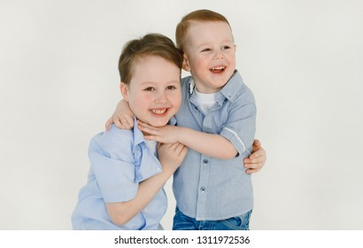 Happy and friendly brothers play. Emotional and funny little boys with a smile hugging each other after playing sitting on the white floor. Happy childhood. Lifestyle. Positive emotions and energy