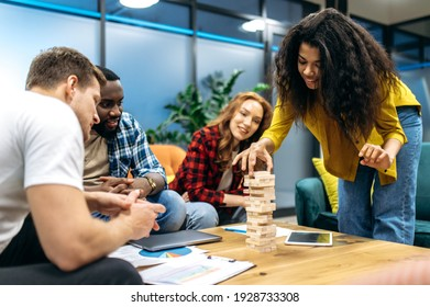 Happy friendly business people playing in office, taking a break. Joyful multiethnic coworkers having fun, resting from tense brainstorm, distracted from work or study