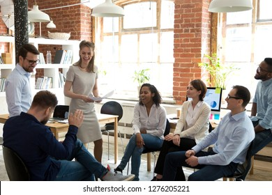 Happy friendly business team having fun at corporate training, funny teambuilding activity, diverse employees group laughing at briefing, colleagues joking together at meeting, staff good relations