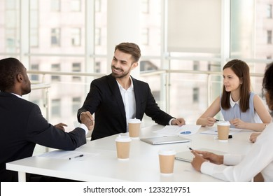 Happy friendly caucasian businessman shake hand of african partner greeting, closing deal, welcoming at office meeting, diverse employees handshake celebrate collaboration or successful negotiation