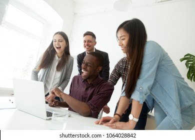 Happy friendly diverse millennial team laughing watching joke on laptop, excited multiracial employees having fun together, african, caucasian and asian coworkers enjoy funny online humor on computer
