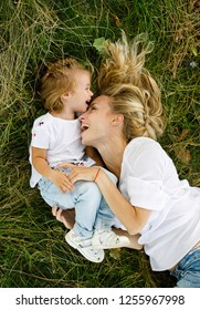 Happy and friendly family in nature. Beautiful and cheerful young mother plays and frolics with her little blonde daughter lying on the grass for a walk on a summer day. Positive emotions. Summertime