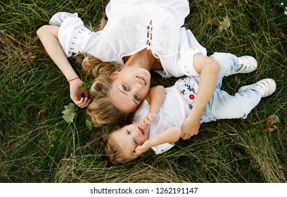Happy and friendly family in nature. Emotional and young mother with blond hair hugs her smiling little daughter lying on the grass. Summer park. Positive emotions.Childhood. Summertime.Lifestyle