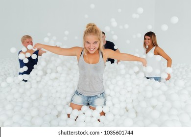 Happy Friendly family surrounded by white plastic balls in the dry pool. Spend fun time. Adult childhood at Playground with pit-ball. girl throws balls.