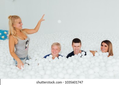Happy Friendly family surrounded by white plastic balls in the dry pool. Spend fun time. Adult childhood at Playground with pit-ball.