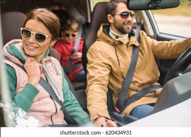 Happy friendly family traveling by car on rural road