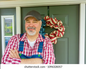 Happy friendly farmer with a goatee wearing patriotic colors celebrating 4th July Independence Day in America standing beside a wreath in the colors of the Stars and Stripes flag