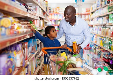 Happy friendly glad  cheerful positive smiling  African family of father and tween son shopping together in supermarket