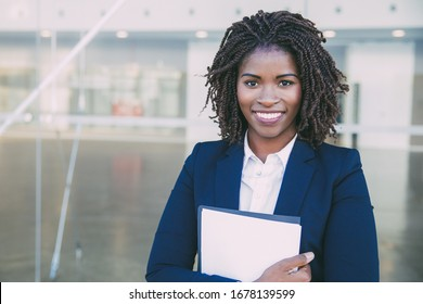 Happy friendly legal expert posing outside. Young black business woman standing at glass wall, holding documents, looking at camera, smiling. Legal expert concept