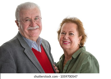 Happy friendly loving senior couple standing close together in an embrace smiling happily at the camera isolated on white