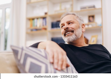 Happy friendly man looking back over his shoulder with a smile as he relaxes on a comfortable sofa at home