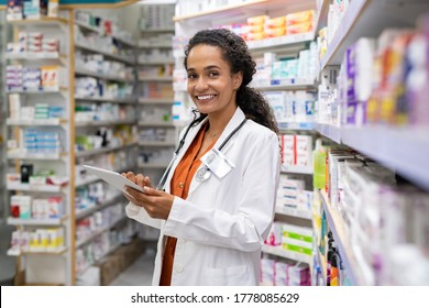 Happy friendly multiethnic pharmacist doing inventory in a provided and modern pharmacy while looking at camera. Portrait of smiling african doctor woman working in drugstore with digital tablet.