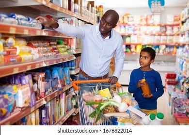 Fröhlich freundliche, angenehme afrikanische Familie des Vaters und zwischen Sohn Shopping zusammen im Supermarkt