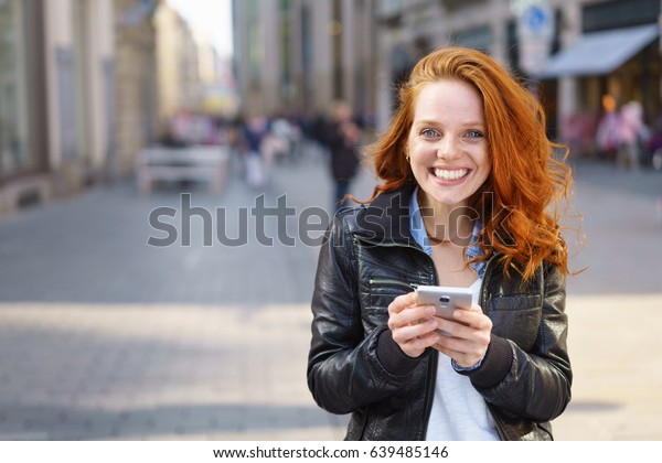 Happy friendly pretty young redhead woman using her mobile phone outdoors in an urban street as she stands grinning at the camera, with lateral copy space