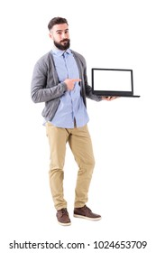 Happy friendly stylish man advertising blank white laptop screen. Full body length portrait isolated on white studio background.