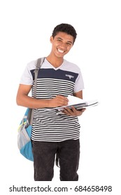 Happy friendly teenage boy with backbag smiling and holding a notebook, teenager wearing striped gray t-shirt and black jeans,  isolated on white background