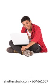 Happy friendly teenage boy sitting down and using the laptop, teenager wearing red shirt and black jeans,  isolated on white background