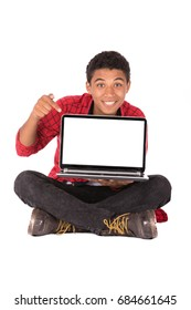Happy friendly teenage boy sitting down and holding a laptop, teenager wearing red shirt and black jeans,  isolated on white background