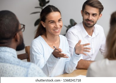 Happy friendly woman team leader coach mentor talking to employees group at office meeting smiling offering idea teaching interns or reporting at briefing seminar having fun business conversation