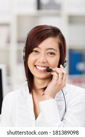 Happy friendly young Asian call centre operator smiling at the camera as she listens to the customer speaking on her headset