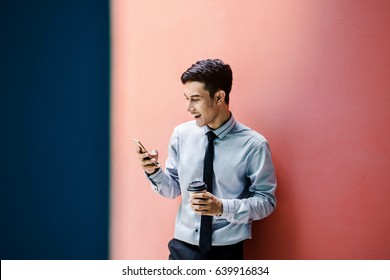Happy and friendly young attractive Businessman use a Smart phone and holding morning coffee at colorful wall, Social communicate technology in business concept, Lifestyle of modern male