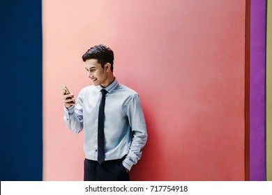 Happy and friendly young attractive Businessman use a Smart phone and Smiling at colorful wall, Social communicate technology in business concept, Lifestyle of modern male