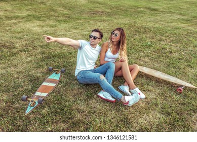Happy friendly young couple woman and man, sit summer on grass in city park. skateboards, longboard. Concept teenagers are teenagers, trendy and stylish in casual wear. Rest on weekend lifestyle.