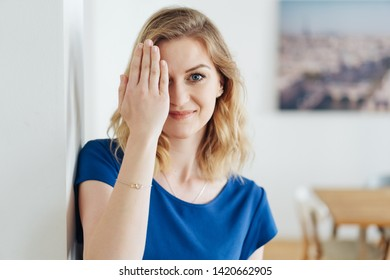Happy friendly young woman covering on eye with her hand as she leans against an interior wall at home