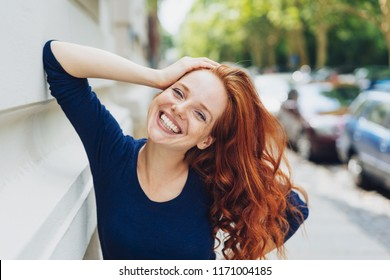Happy friendly young woman leaning on a building in an urban street with her head tilted to the side grinning at the camera with a vivacious smile