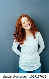 Happy friendly young woman with a lovely smile and long wavy red hair posing over a dark studio background with copy space