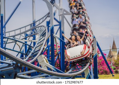 Happy friends in amusement park on a summer day