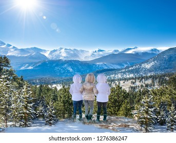 Happy friends with arms around each other enjoying beautiful  mountain view on winter  hiking trip. Rocky Mountain National Park. Close to Estes Park, Colorado, USA
