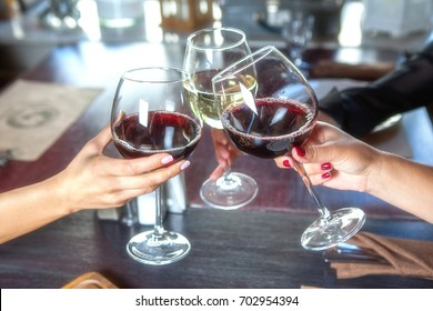 happy friends in a bar drinking red wine. Focus on glasses