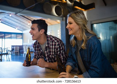 Happy friends with beer bottles looking away at restaurant