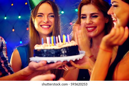 Happy friends birthday celebrating food with candle celebration cakes in night club. Female people wear in hat party looking at burning candles. Women and men have fun and chatting.
