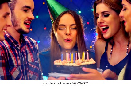 Happy friends birthday party with candle celebration cakes. People looking at burning candles. Two women and men have fun in nightclub.