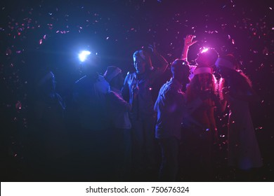Happy friends at birthday party at night club. Classy people enjoying life, dancing, drinking champagne and having fun at dark smoky background, showered with confetti. B-day celebration background