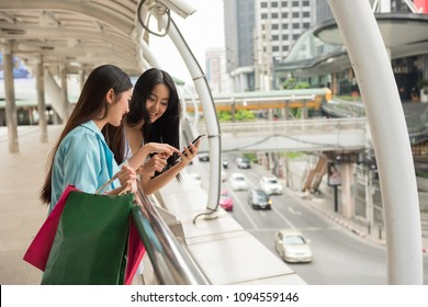 Happy friends browsing retail stores location by 4g internet from smartphone. Two beautiful young Asian women enjoying shopping in summer at modern city. Foreign travellers.