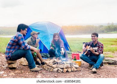 Happy friends camping party playing music and enjoying bonfire in nature and lake, Partying in camping, Asian Young people celebrating during summer vacation, summertime and travel activity concepts