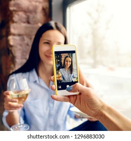 Happy friends celebrate the holiday at home. Woman taking photo her beautiful friend with glass of wine with a smartphone
