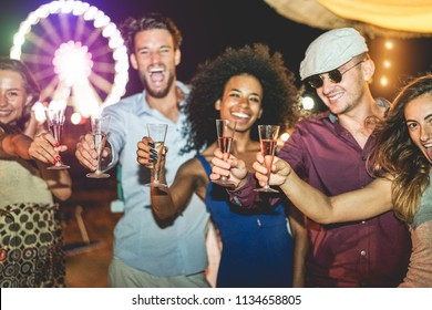 Happy friends celebrating and drinking champagne at beach party outdoor - Young millennial generation people having fun on weekedn night - Youth and summer concept - Focus on black girl hand glass