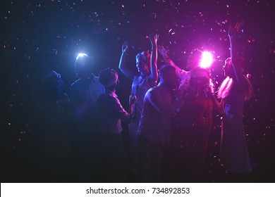 Happy friends celebrating new year at night club. Classy people enjoying life, dancing, drinking champagne and having fun at dark smoky background, showered with confetti. Christmas party background
