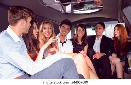 Happy friends chatting in limousine on a night out