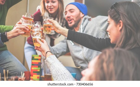 Happy friends cheering with beer and playing board games in bar pub restaurant - Young people toasting appetizer in brewery chalet - Concept about good and positive mood - Focus on left bottom hand